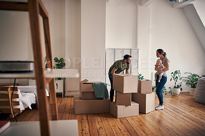 Buy stock photo Full length shot of an affectionate young father lifting boxes while his wife is carry their baby in their new home on moving day