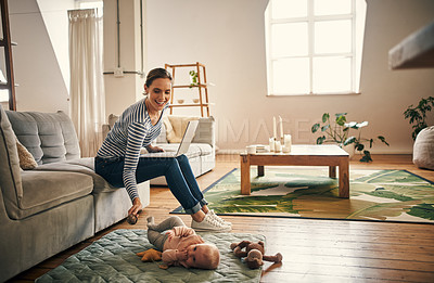 Buy stock photo Full length shot of an affectionate young mother being playful with her little baby girl while using a laptop in their living room at home