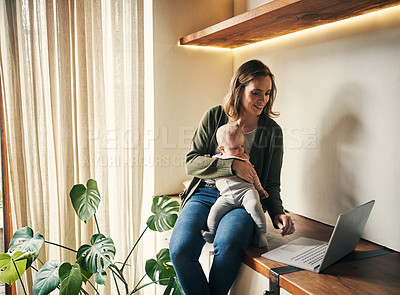 Buy stock photo Cropped shot of an affectionate young mother using a laptop while holding her little baby girl at home