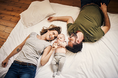 Buy stock photo High angle shot of an affectionate young couple being playful with their little baby girl while lying on a bed at home