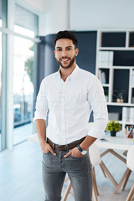 Buy stock photo Cropped portrait of a handsome young businessman standing alone in his office with his hands in his pockets