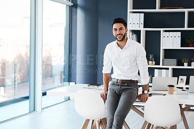 Buy stock photo Cropped portrait of a handsome young businessman sitting on his desk in his office alone