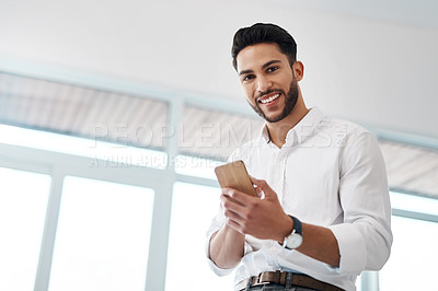 Buy stock photo Cropped portrait of a handsome young businessman sitting alone in his office and texting on his cellphone