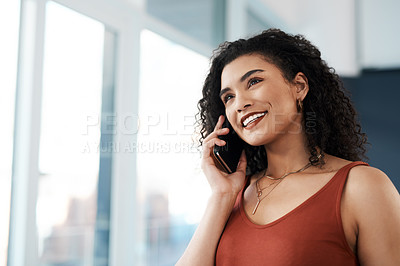 Buy stock photo Cropped shot of an attractive young businesswoman standing in her office and talking on her cellphone