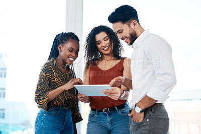 Buy stock photo Cropped shot of a diverse group of businesspeople standing in the office together and using a tablet