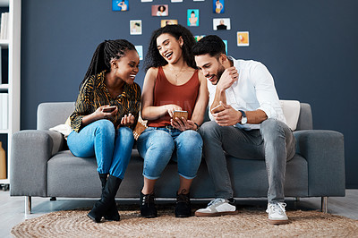 Buy stock photo Full length shot of a diverse group of business colleagues sitting on a sofa together and using a cellphone