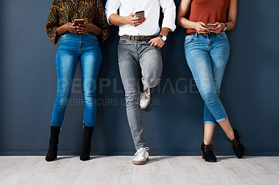Buy stock photo Cropped shot of an unrecognizable group of businesspeople standing against a gray background in the studio and using their cellphones