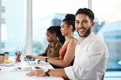 Buy stock photo Cropped portrait of a handsome young businessman sitting in the office while his colleagues work on laptops behind him