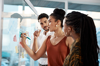 Buy stock photo Cropped shot of a diverse group of businesspeople standing and using a glass board with post-its in the office