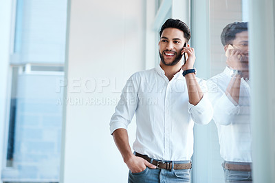 Buy stock photo Cropped shot of a handsome young businessman standing in his office and talking on his cellphone