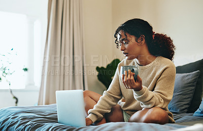 Buy stock photo Shot of an attractive young woman drinking coffee while using her laptop