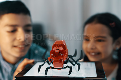 Buy stock photo Cropped shot of two young siblings looking at and admiring their robotic toy spider at home