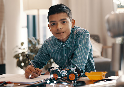 Buy stock photo Portrait of a handsome young boy doing his homework on robotics at home