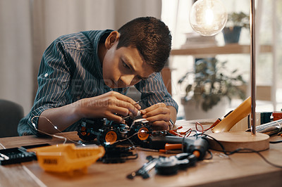 Buy stock photo Shot of a handsome young boy building a robotic toy car at home