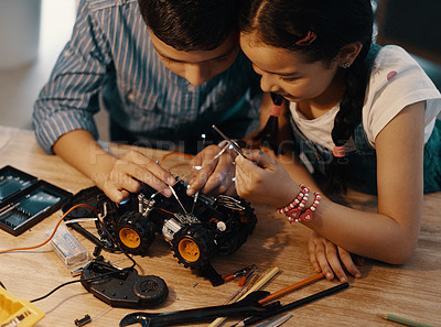 Buy stock photo Cropped shot of two adorable young siblings building a robotic toy car together at home