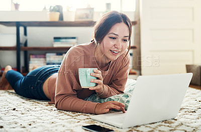 Buy stock photo Full length shot of an attractive young woman lying on the floor and using her laptop at home