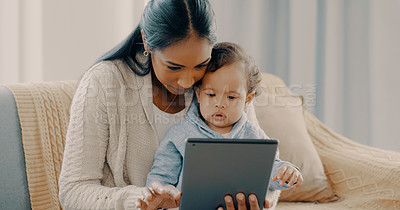 Buy stock photo Shot of a young mother using a digital tablet while spending time with her baby boy at home