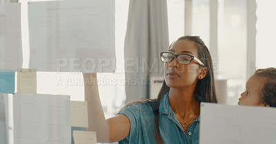 Buy stock photo Shot of a young businesswoman holding her baby and brainstorming ideas on a glass wall inside her office