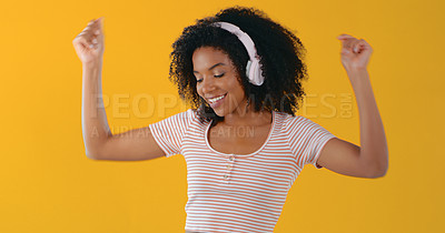 Buy stock photo Cropped shot of a young woman listening to music through her headphones against a yellow background