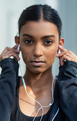 Buy stock photo Portrait of a sporty young woman listening to music while exercising outdoors