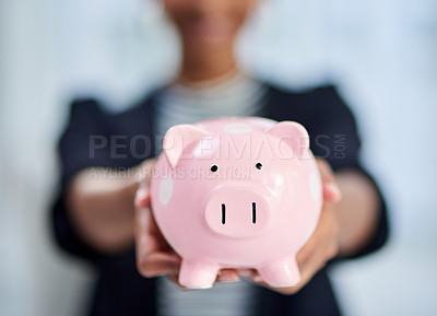 Buy stock photo Cropped shot of an unrecognizable businesswoman holding a piggy bank inside her office