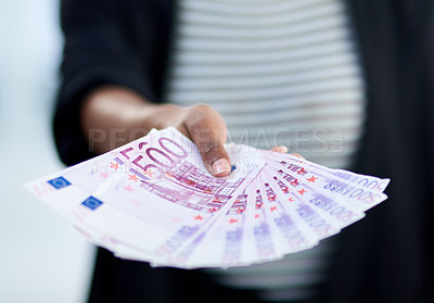 Buy stock photo Cropped shot of an unrecognizable businesswoman holding a stack of money inside her office at work