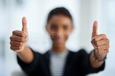 Buy stock photo Defocused shot of a young businesswoman posing with her thumbs up at work
