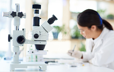 Buy stock photo Shot of a microscope in a lab with a young scientist working in the background