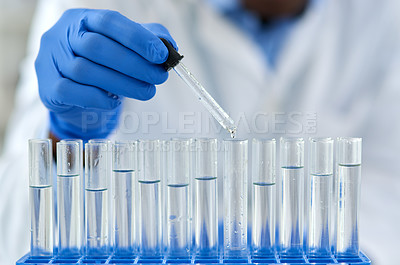 Buy stock photo Closeup of an unrecognizable scientist pouring a substance into test tubes to do experiments on inside of a laboratory during the day
