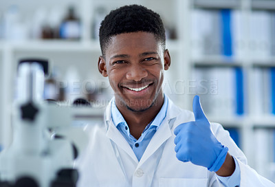 Buy stock photo Portrait of a cheerful young male scientist wearing protective gloves while showing thumbs up inside of a laboratory during the day