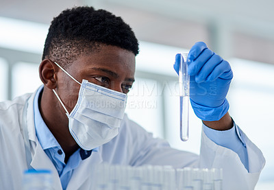 Buy stock photo Cropped shot of an unrecognizable male scientist holding up a test tube and examine's it inside of a laboratory during the day