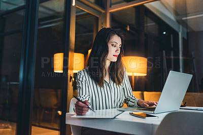 Buy stock photo Shot of a young businesswoman using a laptop and writing notes during a late night at work