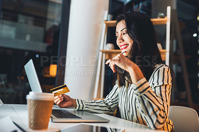 Buy stock photo Shot of a young businesswoman using a credit card and laptop during a late night at work