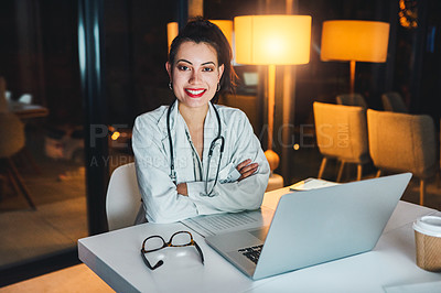 Buy stock photo Shot of a young doctor working at her desk during a late night