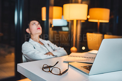 Buy stock photo Shot of a young doctor looking frustrated out while working at her desk late at night