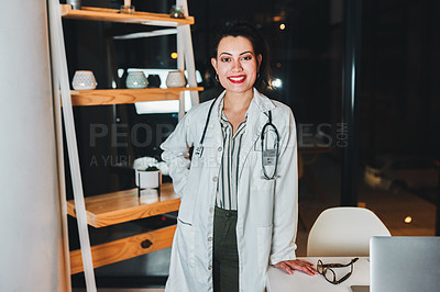 Buy stock photo Shot of a young doctor working in her office late at night