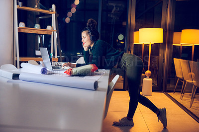 Buy stock photo Full length shot of an attractive young female architect listening to music while using a laptop in a modern office at night