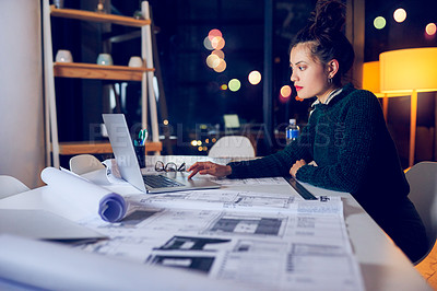 Buy stock photo Cropped shot of an attractive young female architect using a laptop while working late in a modern office