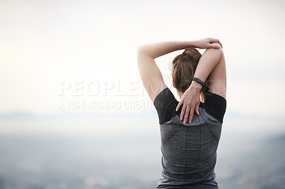 Buy stock photo Rearview shot of a sporty young woman stretching her arms while exercising outdoors