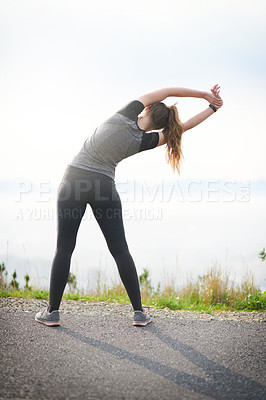 Buy stock photo Rearview shot of a sporty young woman stretching while exercising outdoors