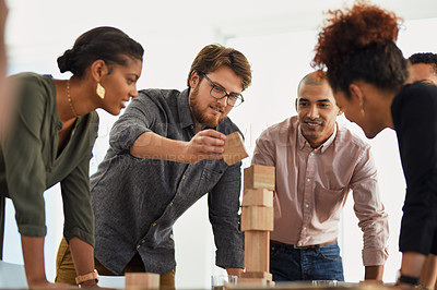 Buy stock photo Shot of a group of businesspeople stacking building blocks together in an office