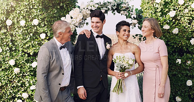 Buy stock photo Cropped shot of an affectionate young newlywed couple standing with their parents on their wedding day