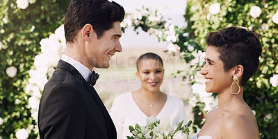 Buy stock photo Cropped shot of an affectionate young couple smiling at each other while saying their vows on their wedding day