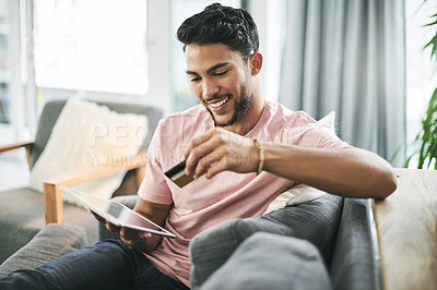 Buy stock photo Shot of a young man using a credit card and digital tablet on the sofa at home