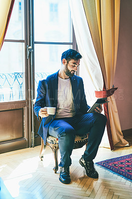 Buy stock photo Full length shot of a handsome young businessman drinking coffee and using a digital tablet inside his hotel room
