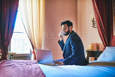 Buy stock photo Shot of a handsome young businessman drinking coffee and using a laptop inside his hotel room