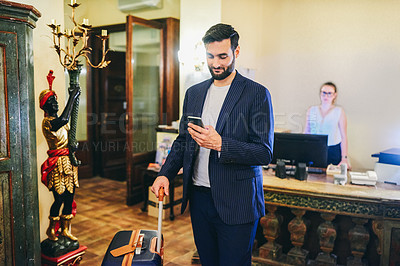 Buy stock photo Shot of a handsome businessman standing with his luggage and using his cellphone at the reception area of a hotel