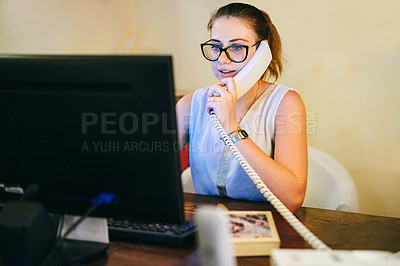 Buy stock photo Shot of an attractive young hotel receptionist making phone calls and working at her desk