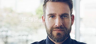 Buy stock photo Cropped portrait of a handsome young businessman looking serious while standing in a modern office
