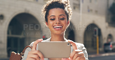 Buy stock photo Cropped shot of an attractive young woman standing alone in the city and using her cellphone to take pictures